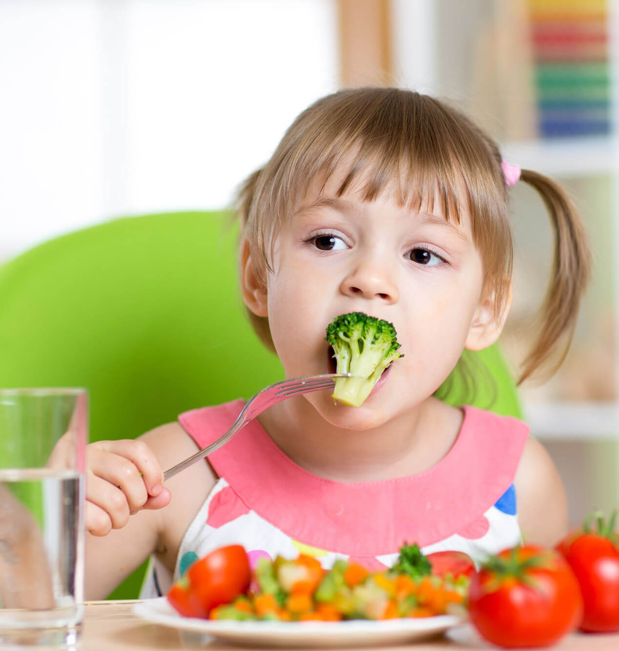little girl eating broccoli
