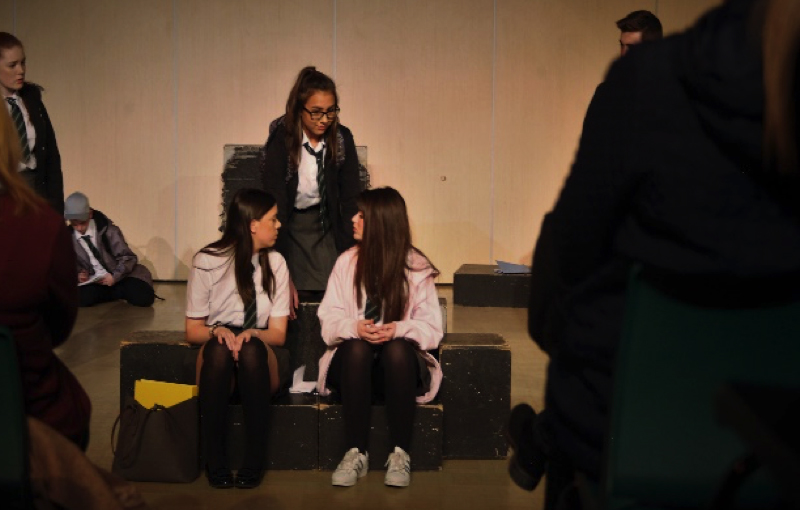 three girls sat together on stage during blue electric wind