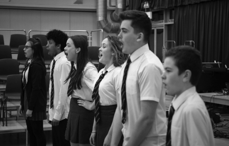 black and white image of a group of boys and girls singing on stage