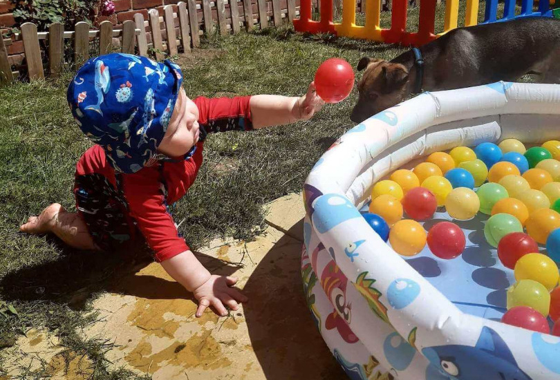 Child playing with water and ball pit