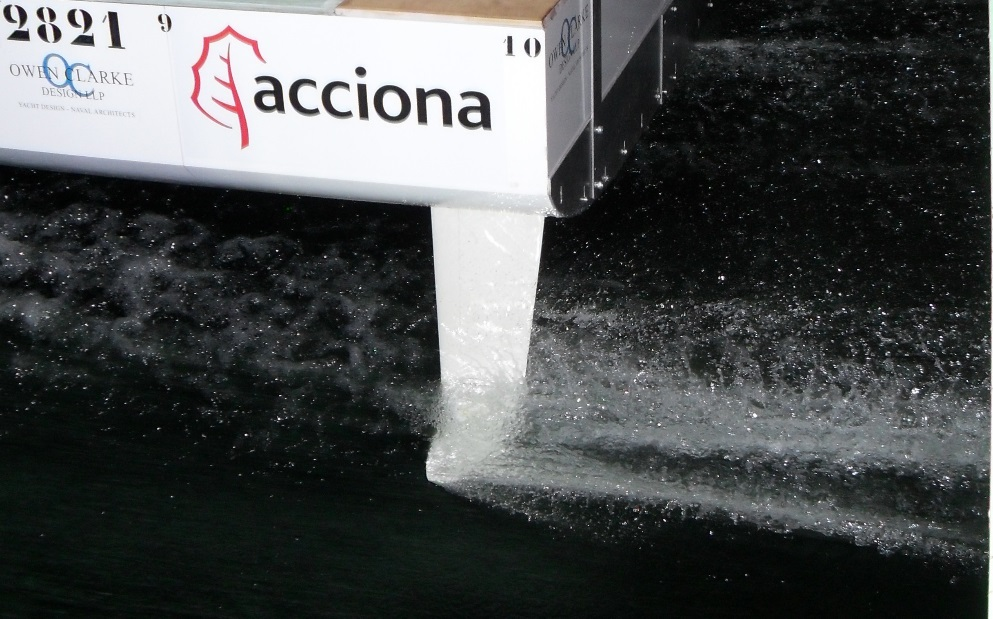 This is a photograph of a T foil rudder at speed, foiling during 1/3rd scale towing tank model testing for an Owen Clarke Design IMOCA 60 racing yacht. The model testing was only initiated after hundreds of simulations by the naval architects using computational fluid dynamics ( CFD ) to reduce the number of candidate hull and foil designs.