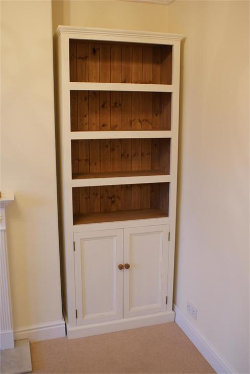 Living room storage / display solution, featuring open shelves over closed shelves behind panelled doors.