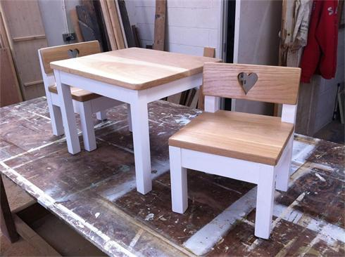 Scaled down dining table and chairs for two children with solid oak table top and seat bases and backs.