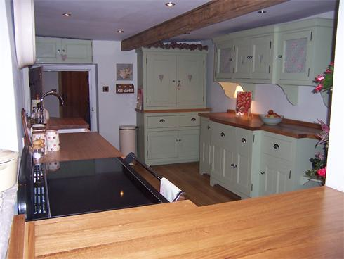 Full kitchen installation featuring customer designed heart details, chrome handles and solid oak worktops.